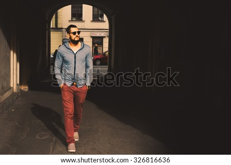 portrait macho sex appeal young guy with a beard and mustache and cardigan posing on the street vintage man, fashion men, hipster street  on a sunny day close-up - stock photo