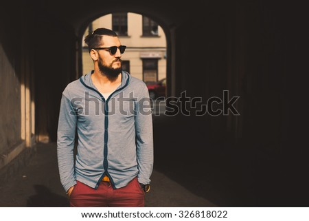 portrait macho sex appeal young guy with a beard and mustache and cardigan posing on the street vintage man, fashion men, hipster street  on a sunny day close-up