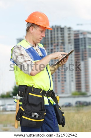 Portrait man construction worker. Male engineer construction. Contractor at a building site. Male construction worker at a building site. Business. Construction foreman working with electronic tablet. - stock photo
