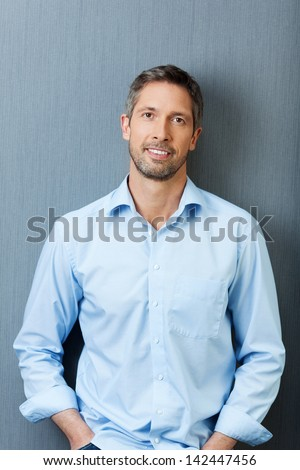 Portrait mature businessman smiling while standing against blue wall - stock photo