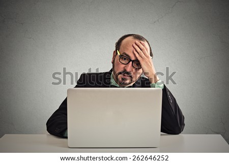 Portrait mature stressed displeased worried business man sitting in front of laptop computer isolated on gray office wall background. Negative face expression emotion feelings problem perception