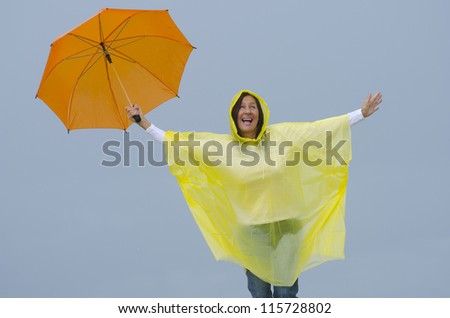 Portrait mature woman standing in the rain, wearing yellow raincoat and orange umbrella, isolated with grey sky as background and copy space. - stock photo