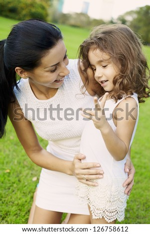 Portrait mom and daughter at the outdoor in real emotions - stock photo