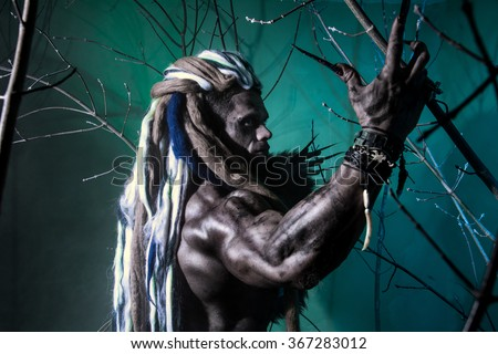 Portrait muscular werewolf with dreadlocks among the branches of the tree. Gothic image of scary diabolical creatures for Halloween
