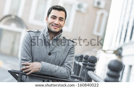Portrait od smiling gorgeous young attractive man, outdoor - outside coldly morning. Beautiful man wearing coat - winter clothing - stock photo