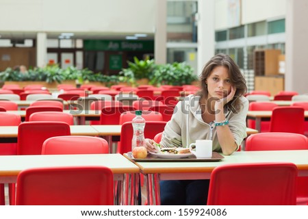 Portrait of a alone and sad female student sitting in the cafeteria with food tray - stock photo