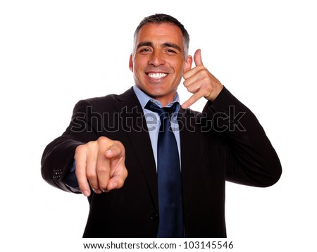 Portrait of a ambitious smiling broker pointing on black suit against white background - stock photo