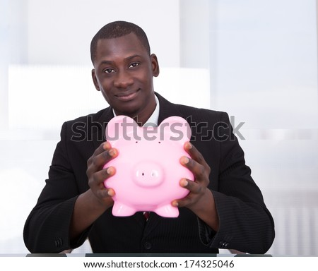 Portrait Of A An African Young Businessman Holding Piggybank