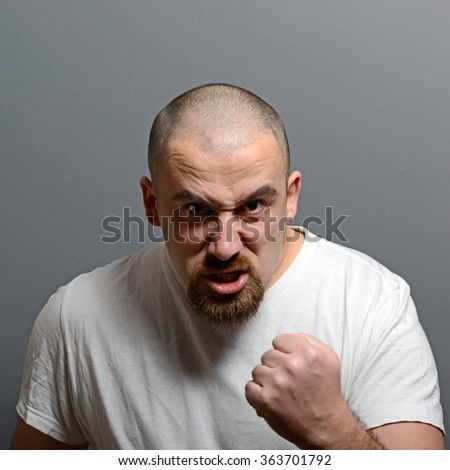 Portrait of a angry man holding fists against gray background - stock photo