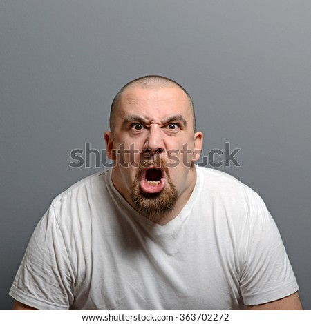 Portrait of a angry man screaming against gray background - stock photo