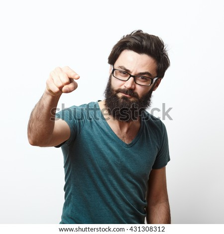 portrait of a angry young man with beard and glasses wearing t-shirt pointing to camera. We need you concept