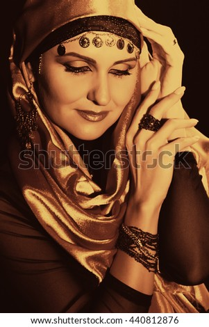Portrait of a arabian beautiful girl hiding her face with an open hand. Feminine woman with a beautiful makeup, oriental beauty. Mysterious East - stock photo
