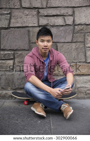 Portrait of a Asian man using his Smart Phone and holding his skateboard. Standing outdoors in city street.