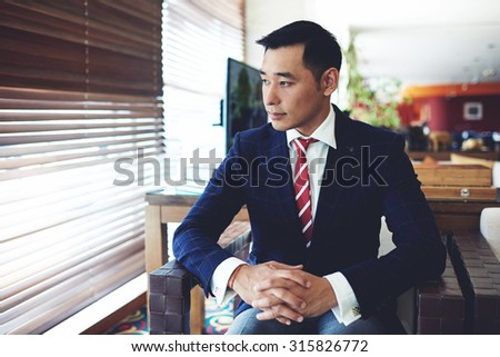 Portrait of a asian men entrepreneur dressed in luxury suit waiting for the colleagues while sitting in office space interior, young managing director in formal wear relaxing after business meeting  - stock photo