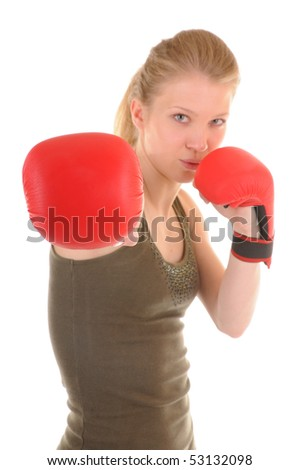 Portrait of a attack girl with red boxing gloves. Focus on nearest glove.