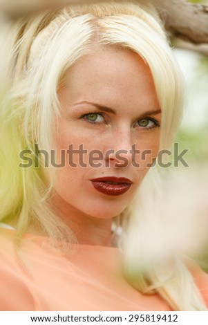 Portrait of a attractive blonde woman at an apple orchard - stock photo