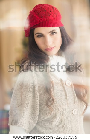 Portrait of a attractive brunette with red hat at home in the living room - stock photo