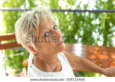 Portrait of a attractive older woman in the beer garden - stock photo