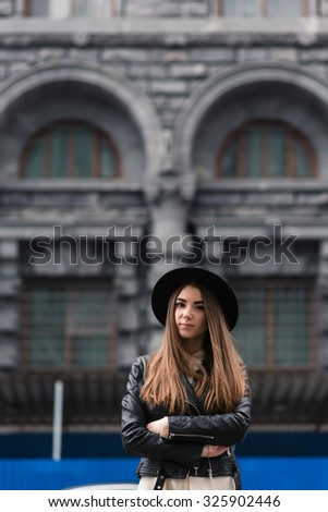 Portrait of a attractive woman with cool style standing on the street while resting after active walking during her weekend, young charming hipster girl with trendy look posing outdoors in autumn day  - stock photo