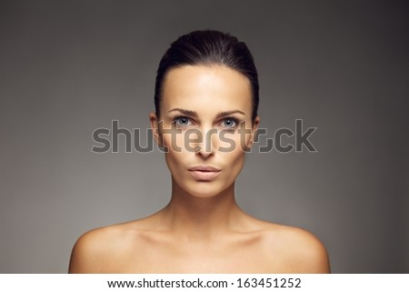 Portrait of a attractive young brunette with grey eyes looking at camera. Beautiful woman with clean and glowing skin isolated on gray background