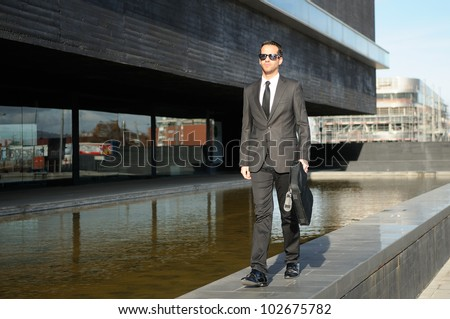Portrait of a attractive young business man walking in the street with a briefcase - stock photo