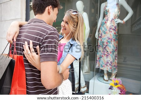 Portrait of a attractive young couple having fun and enjoying a vacation city break, embracing and smiling while shopping in the fashion stores, outdoors. Consumer and travel lifestyle. - stock photo