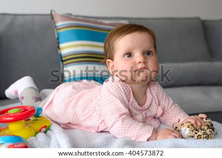 Portrait of a baby girl lying on a blanket - stock photo