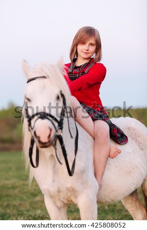Portrait of a baby girl sitting on a white pony Outdoors - stock photo