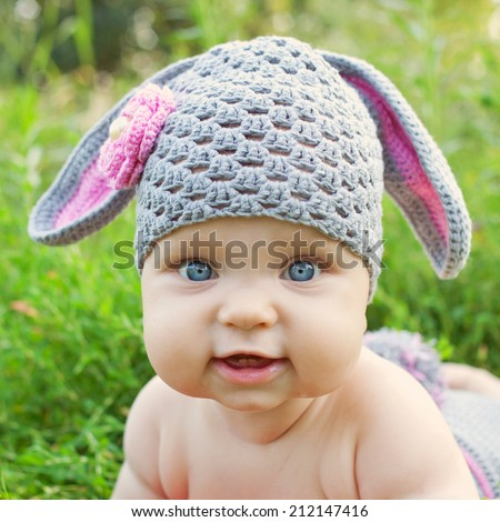 Portrait of a baby in the hat like a bunny or lamb of green grass. Happy childhood outdoors. - stock photo