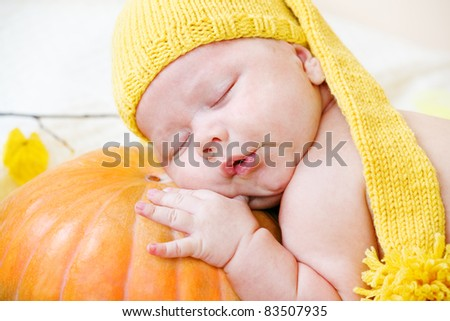 Portrait of a baby in yellow hat using pumpkin as a pillow - stock photo