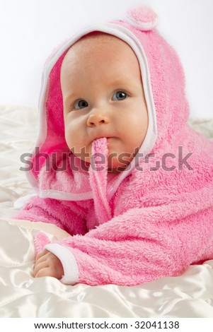 Portrait of a baby lying on the satin blanket - stock photo