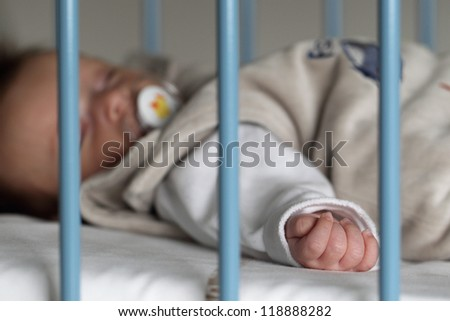 Portrait of a baby, 2 months old, sleeping in a crib to hospital. The focus is on the hand of the baby for a better impact of the message.