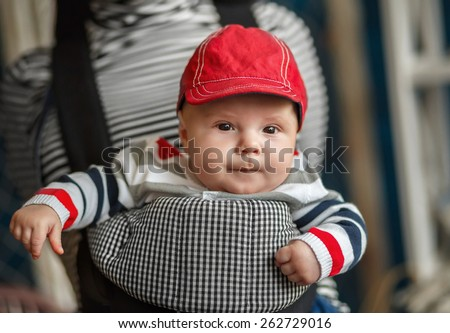 Portrait of a baby sitting in an ergonomic baby carrier - stock photo