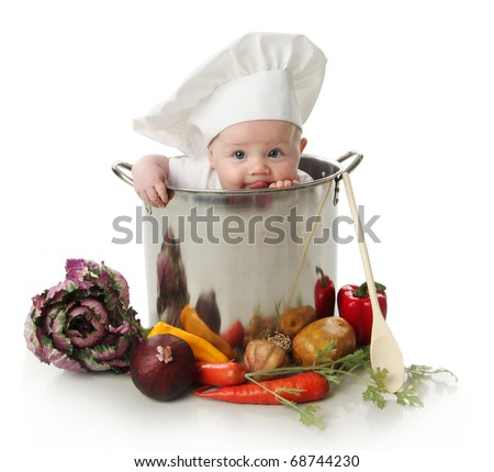 Portrait of a baby sitting wearing a chef hat sitting inside and licking a large cooking stock pot surrounded by vegetables and food, isolated on white - stock photo