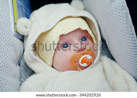 Portrait of a baby sucks a pacifier in the car seat - stock photo