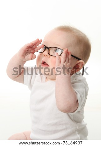 Portrait of a baby wearing eyeglasses and playing with them - stock photo