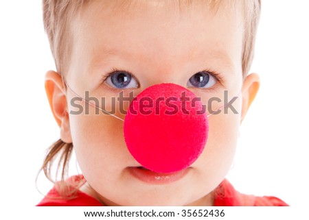 Portrait of a baby with a red clown nose on