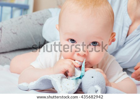 Portrait of a baby with a toy in the mouth. Blue eyes of a child. - stock photo