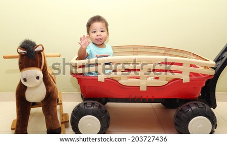 Portrait of a baby with toys looking at the camera - stock photo