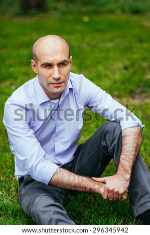 Portrait of a bald and brutal man. Bald guy sitting on the grass in the park. - stock photo