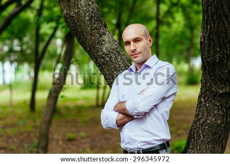 Portrait of a bald and brutal man in the park - stock photo