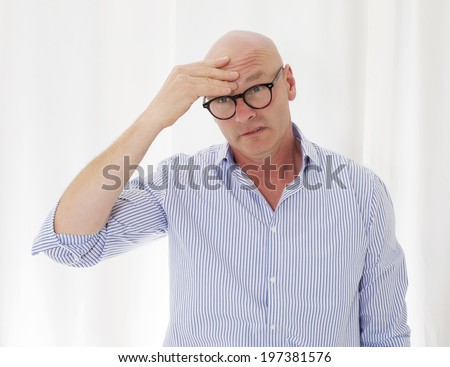 portrait of a bald-headed man with a headache - stock photo