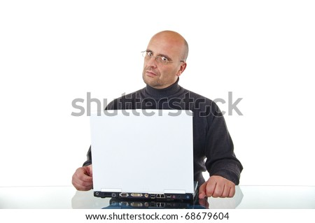 Portrait of a bald man sitting by his laptop working, looking serious and angry - stock photo