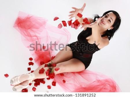 portrait of a ballerina catching fake flower petals - stock photo