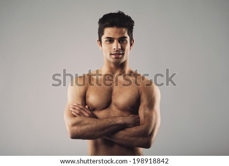 Portrait of a bare-chested muscular man standing with his arms crossed. Fit and masculine young hispanic man shirtless on grey background. - stock photo