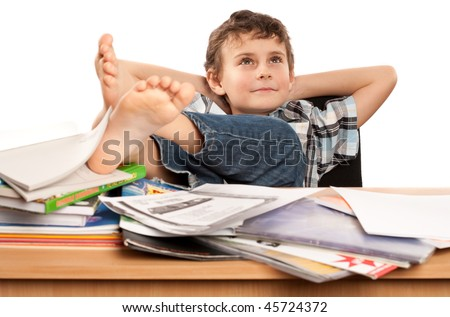Portrait of a barefoot schoolboy with his feet up on his desk, waiting for holiday to come