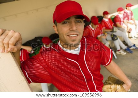 Portrait of a baseball player smiling with team in background - stock photo