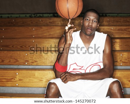 Portrait of a basketball player ball spinning ball on finger  - stock photo