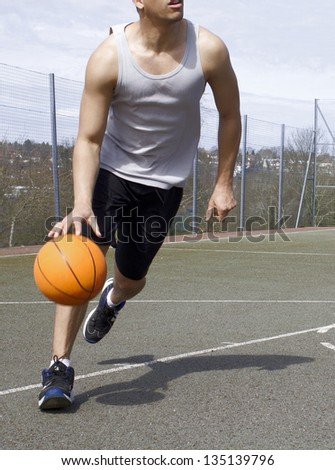 Portrait of a Basketball Player dribbling the ball - stock photo