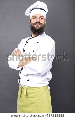 Portrait of a bearded chef with arms folded over gray background